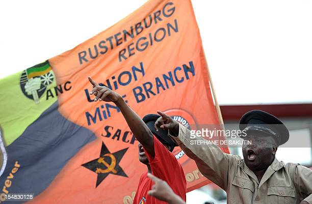 Members of the Congress of South African Trade Unions shout slogans as they gather for a rally in Rustenburg northwest of Johannesburg on October 27...