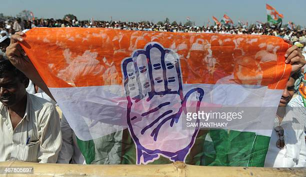 Members of the Congress party hold the party flag during a rally at the conclusion of the Vikas Khoj Yatra at the place where Sardar Vallabhbhai...