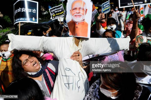 Members of the Congress women's wing carry the effigy of Prime Minister Narendra Modi and Delhi Chief Minister Arvind Kejriwal to burn during a...