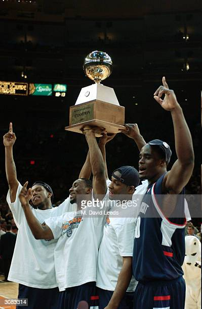 Members of the Connecticut Huskies hold the trophy following their 6158 victory over the Pittsburgh Panthers during the Big East Men's Basketball...