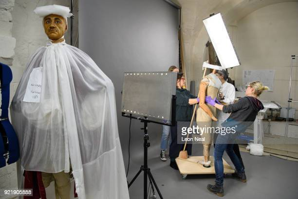 Members of the conservation team check their progress during the fitting of a 'pair of straight bodies' to the funeral effigy of Elizabeth I at...