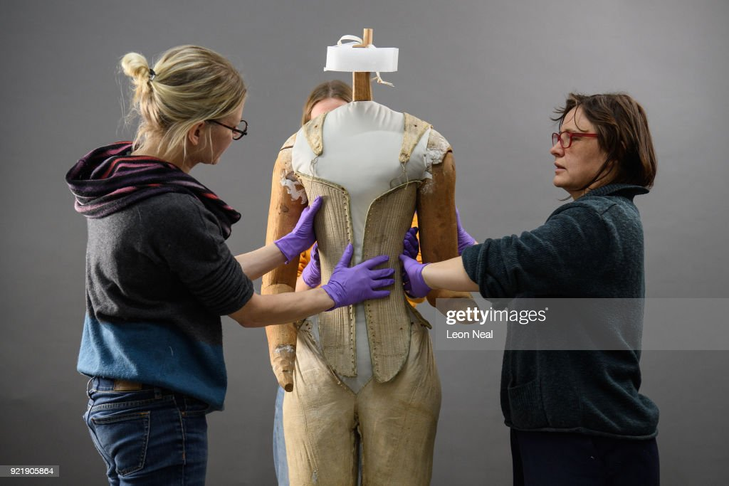 Members of the conservation team wear protective gloves during the fitting of a 'pair of straight bodies' to the funeral effigy of Elizabeth I at Westminster Abbey on February 20, 2018 in London, England. The bodice was supplied by the Queen's tailor, William Jones, to Elizabeth's own pattern and was made especially for the effigy which was carried on the hearse at her funeral in 1603. Among the details discovered during conservation work is that the boning finishes slightly lower on the right-hand side, allowing right-handed Elizabeth greater ease of movement. The corset will be among 300 objects from the Abbey collection on display in The Queen's Diamond Jubilee Galleries when they open at Westminster Abbey in June.