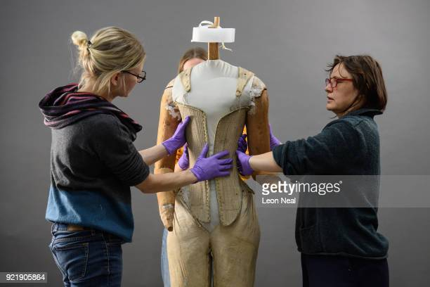 Members of the conservation team wear protective gloves during the fitting of a 'pair of straight bodies' to the funeral effigy of Elizabeth I at...