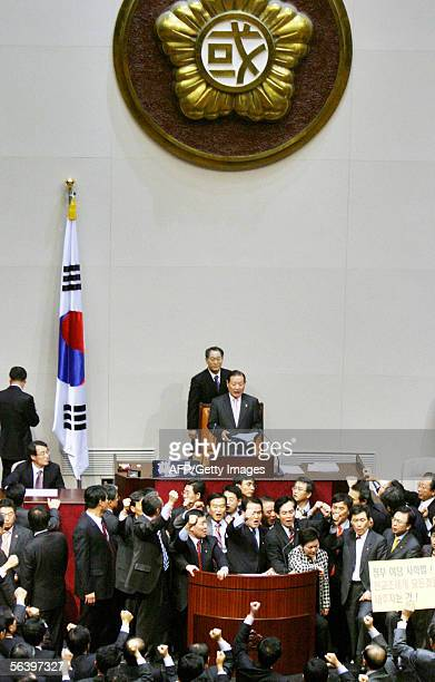 Members of the conservative Grand National Party chant slogans as speaker Kim WonKi looks on after some GNP lawmakers were removed from the speaker's...