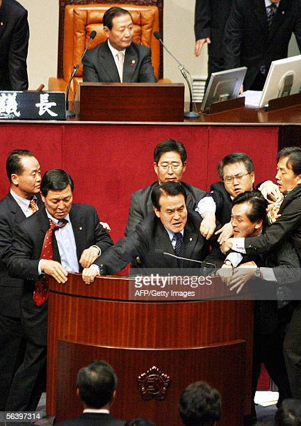 Members of the conservative Grand National Party scuffles with the ruling Uri Party's lawmakers as speaker Kim WonKi looks on after some GNP...
