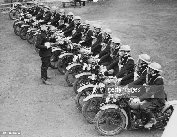 Members of the corps of motorcycle dispatch riders for the Auxiliary Fire Service of the London Fire Brigade undergo training with instructors...