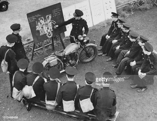 Members of the corps of motorcycle dispatch riders for the Auxiliary Fire Service of the London Fire Brigade undergo engine maintenence training with...