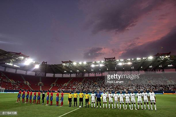 Members of the Costa Rican and Iraqi teams stand with the officials as each team's National Anthem is played before the men's football preliminary...