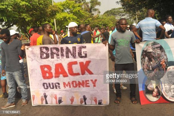 Members of the Council of Patriots hold posters as they protest against the deepening economic crisis under Liberian President George Weah, in...