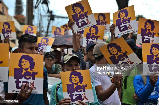 Members of the Council of Popular and Indigenous Organizations of Honduras hold posters with an image of slain indigenous leader and environmental...