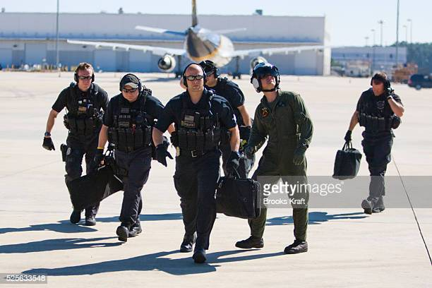 Members of the Counter Assault and Tactical Division of the Secret Service board a helicopter in Houston as they follow President Obama.