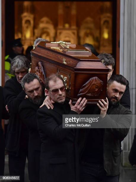 Members of The Cranberries Fergal Lawler Noel Hogan and Mike Hogan help carry Dolores O'Riordan's remains from St Joseph's church on January 21 2018...