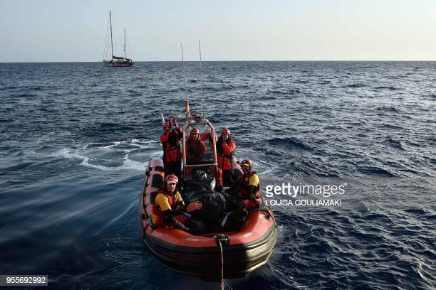 Members of the crew and the captain of Proactiva Open Arms boat in a dinghy applaud as they thank the MV Aquarius a rescue vessel chartered by...