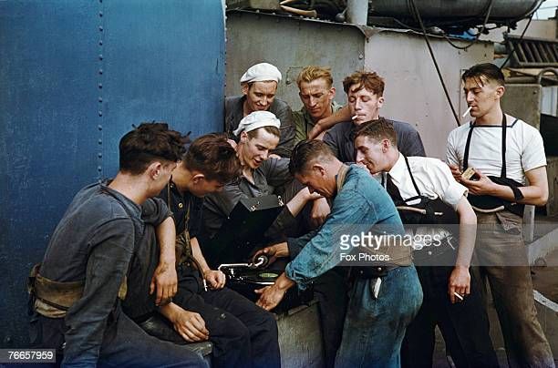 Members of the crew of a Royal Navy ship listen to a gramophone while on patrol in the Atlantic circa 1943
