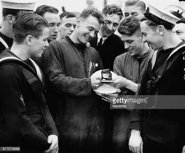 Members of the crew of the British Royal Navy Leanderclass light cruiser HMS Ajax with a piece of shrapnel from a shell fired by the German cruiser...