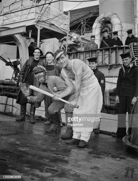 Members of the crew play a game of baseball with kit left on an ex United States Navy destroyer on convoy duty with the Royal Navy in the Atlantic...