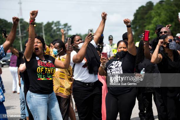 Members of the crowd cheer when a group of black motorcyclists circled the street outside a memorial and public viewing for George Floyd on June 6,...