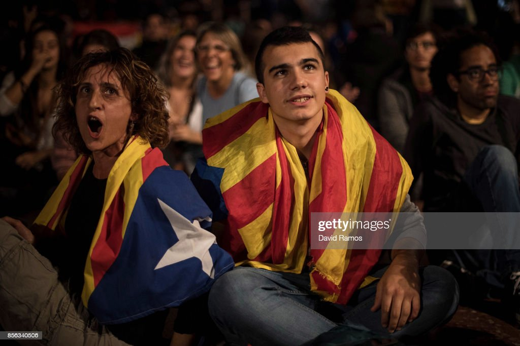 Members of the crowd draped in a Catalan Pro-independence flag react as they watch a large screen showing the speech of the Spain's Prime Minister Mariano Rajoy at Plaza Catalunya on October 1, 2017 in Barcelona, Spain. More than five million elegible Catalan voters are estimated to visit 2,315 polling stations today for the Catalonia's referendum on independence from Spain. The Spanish government in Madrid has declared the vote illegal and undemocratic.