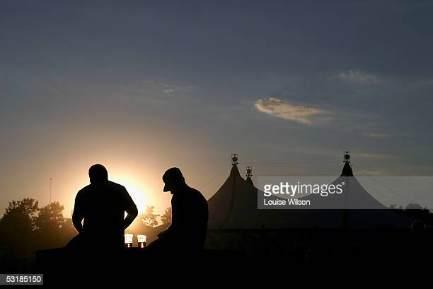 Members of the crowd enjoy a beer as the sun sets over a tent at the Roskilde Festival 2005 on July 1 2005 in Roskilde Denmark Some 70000 people from...