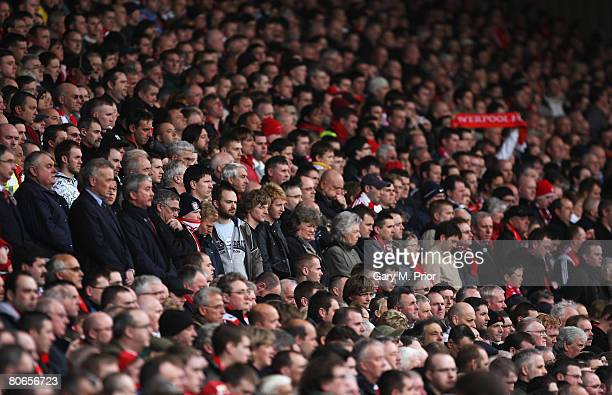 Members of the crowd including Liverpool Chief Executive Rick Parry and former Liverpool Chairman David Moores hold a minute's silence as a mark of...