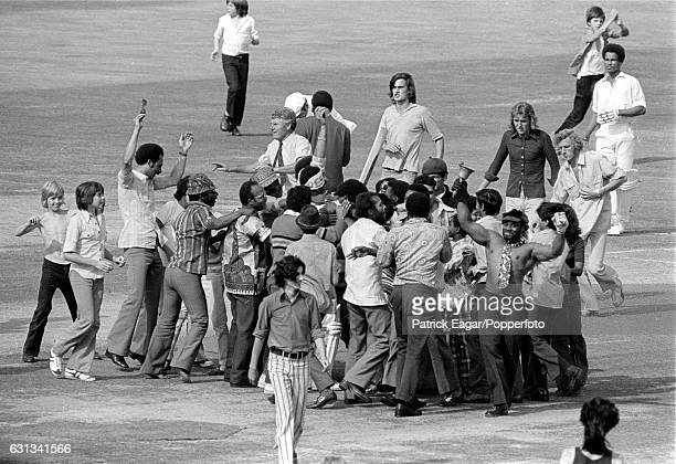 Members of the crowd run on to the pitch to congratulate West Indies batsman Bernard Julien on reaching his first Test century during the 3rd Test...