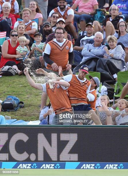 Members of the crowd try to take a catch during the third Twenty20 international cricket match between New Zealand and the West Indies at Bay Oval in...