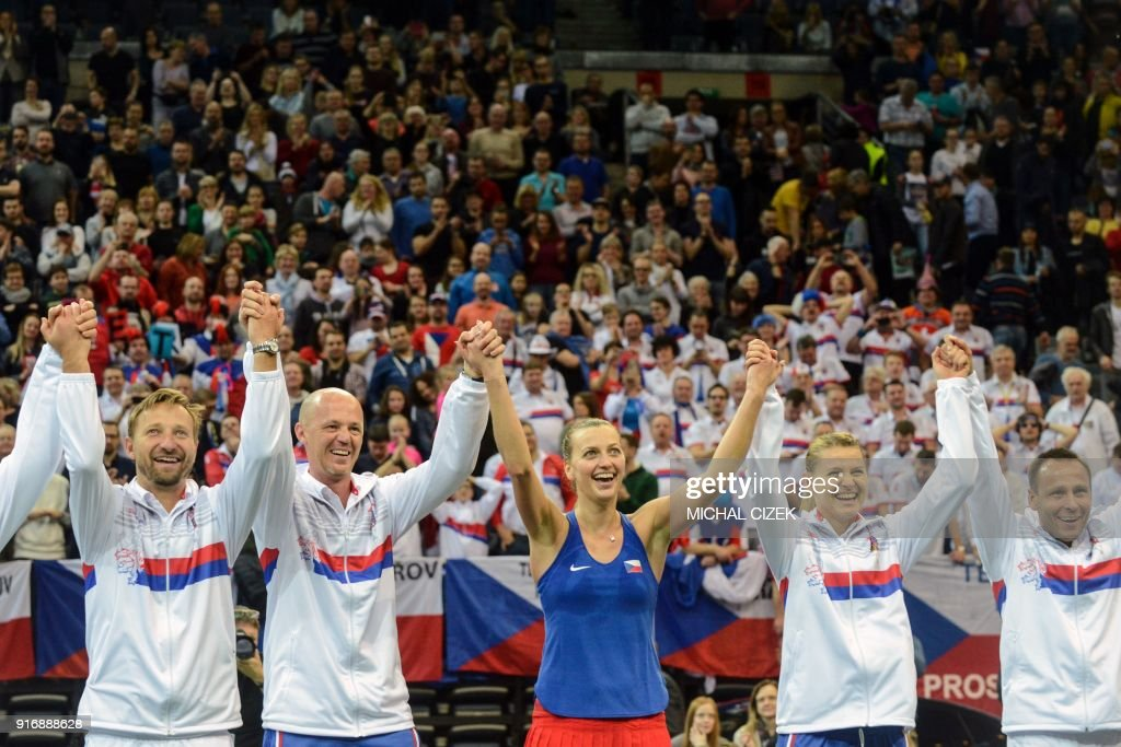 Members of the Czech team celebrate after Petra Kvitova (C) won against Swiss Belinda Bencic during the first round of the International Tennis Federation Fed Cup match between Czech Republic vs Switzerland on February 11, 2018 in Prague. / AFP PHOTO / Michal Cizek