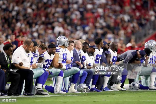 Members of the Dallas Cowboys link arms and kneel during the National Anthem before the start of the NFL game against the Arizona Cardinals at the...