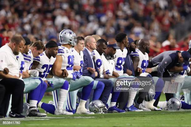 Members of the Dallas Cowboys link arms before the National Anthem at the start of the NFL game against the Arizona Cardinals at the University of...