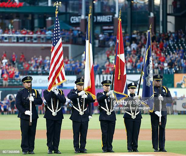 Members of the Dallas Police Department's honor guard present the colors during the national anthem as the Texas Rangers welcome the Oakland...