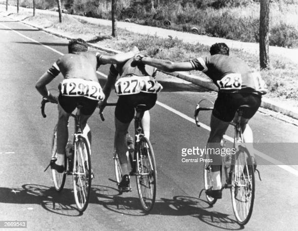 Members of the Danish cycling team trying to steady team mate Knud Enemark before he collapsed during the 100 kilometre trial race in the Rome...