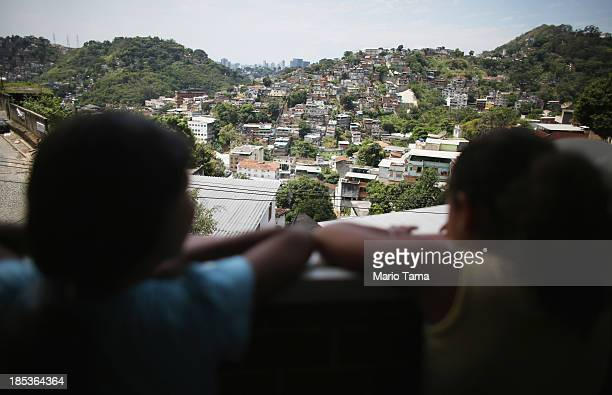 Members of the Das Neves family look out of their home in the Prazeres favela on October 19, 2013 in Rio de Janeiro, Brazil. The family participates...