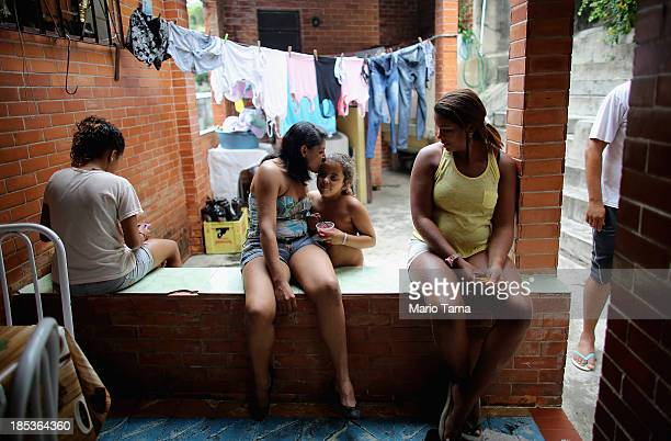 Members of the Das Neves family sit in their home in the Prazeres favela on October 19 2013 in Rio de Janeiro Brazil The family participates in...