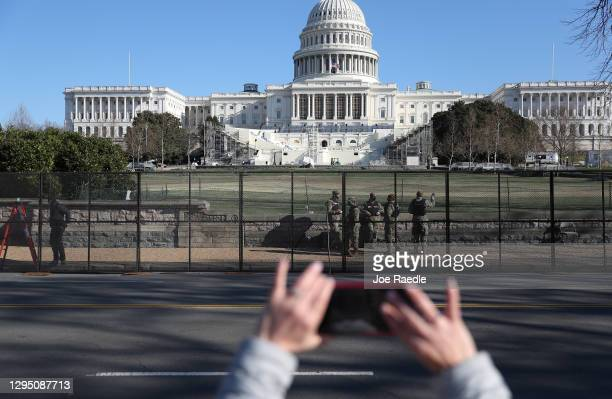 Members of the D.C. National Guard are seen outside the U.S. Capitol Building as workers construct a fence a day after a pro-Trump mob broke into the...