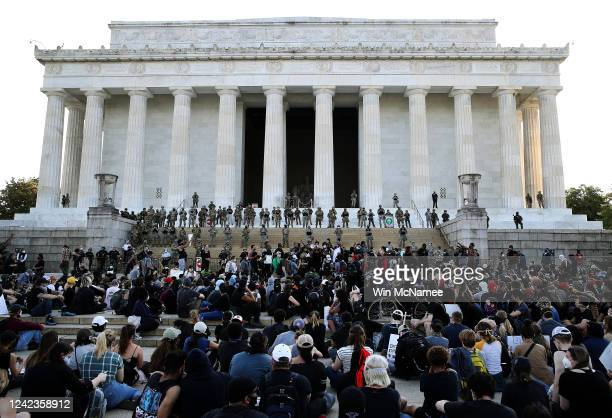 Members of the D.C. National Guard stand on the steps of the Lincoln Memorial monitoring a large crowd of demonstrators participating in a peaceful...