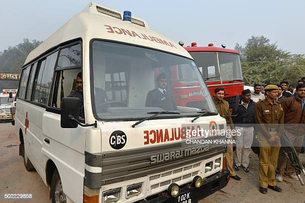 Members of the Delhi Police stand alongside an ambulance at the crash site of a chartered army plane close to the main airport in New Delhi on...