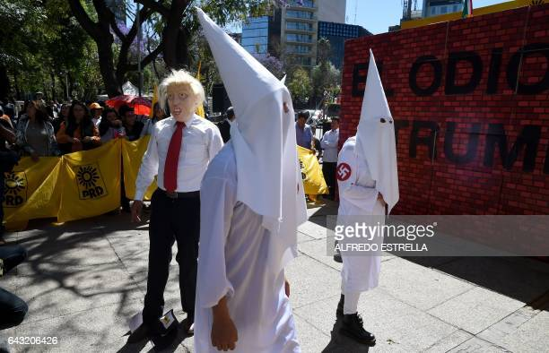 Members of the Democratic Revolution Party wearing a mask of US President Donald Trump and dressed as Ku Klux Klan members protest in front the US...