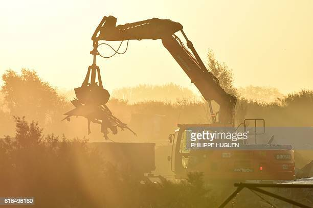 TOPSHOT Members of the demolition crew stand near excavators tearing down the 'Jungle' migrant camp in Calais northern France on October 27 during a...