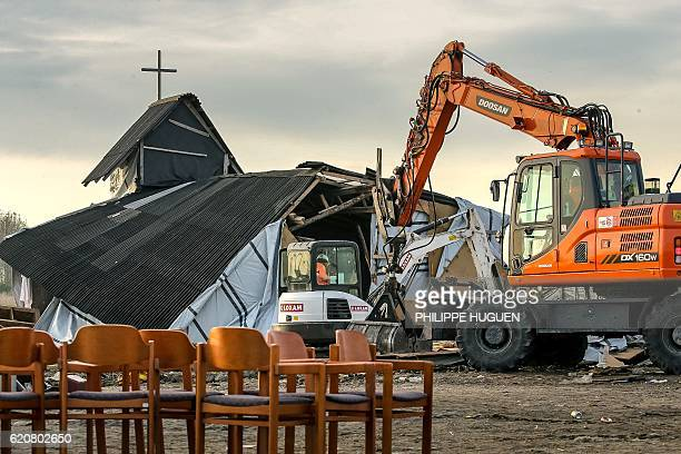 Members of the demolition crew tear down the Orthodox church inside the 'Jungle' migrant camp in Calais northern France during a massive operation to...