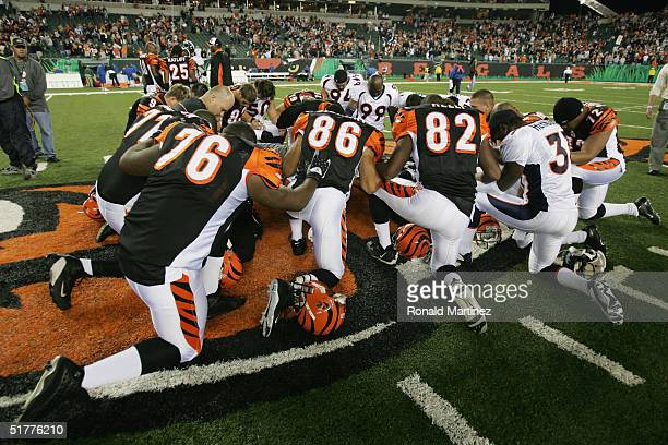 Members of the Denver Broncos and the Cincinnati Bengals come together to pray after their game on October 25 2004 at Paul Brown Stadium in...