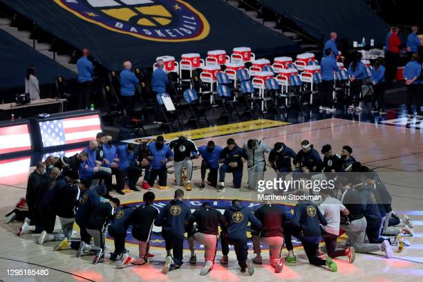 Members of the Denver Nuggets and the Dallas Mavericks kneel at center court for the playing of the National Anthem at Ball Arena on January 07, 2021...