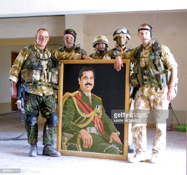 Members of the Desert Rats Zulu Company British Royal Fusiliers pose with a portrait of Iraqi leader Saddam Hussein taken from the local Ba'ath Party...