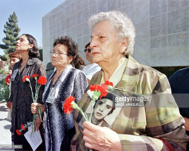 Members of the Detained and Disappeared Human Rights Group stand in front of the Memorial of the Disappeared with carnations and pictures of their...