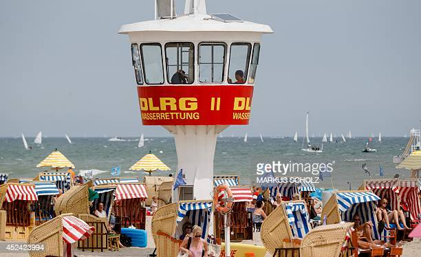 Members of the DLRG German lifeguard organization sit in a tower to survey the Baltic Sea beach in Travemuende northern Germany on July 20 2014 As...
