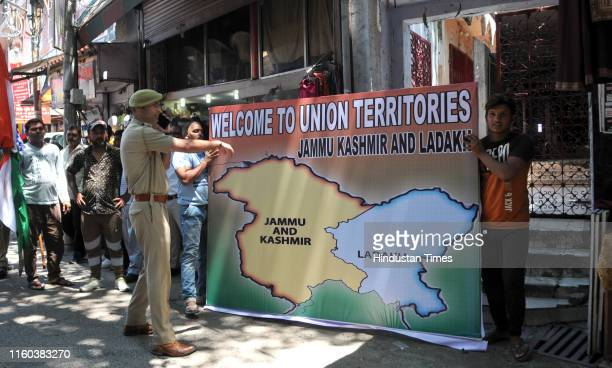Members of the Dogra Front hold a poster showing the two union territories Jammu and Kashmir and Ladakh before a protest demonstration on August 8...