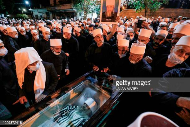 Members of the Druze community gather round the body of late spiritual leader Hassan Halabi, who died at the age of 75 of complications of COVID-19...