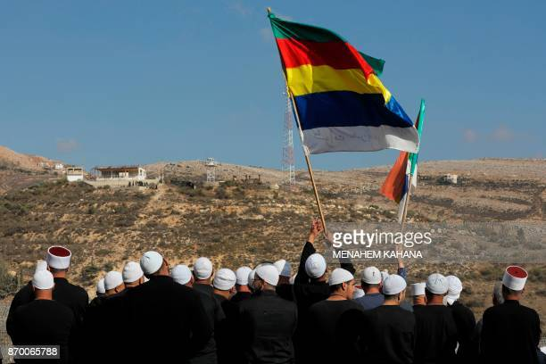 Members of the Druze community residing in Majdal Shams in the Israeli-occupied sector of the Golan Heights wave at their Syrian Druze friends and...