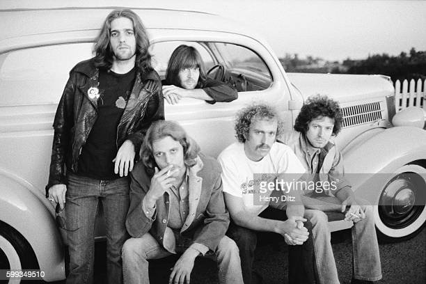 Members of The Eagles stand around a vintage car. Members are, clockwise, Glen Frey, Randy Meisner, Don Henley, Bernie Leadon, and Don Felder.