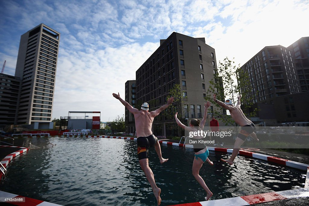 Members of the East German Ladies' swimming team jump in the new 'King's Cross Pond Club' outdoor swimming pool on May 22, 2015 in London, England. The 40 metre pool is purified using submerged plants to filter the water and is surrounded by flowers and plants. It is open to members of the public Monday and Friday between 6am and dusk.