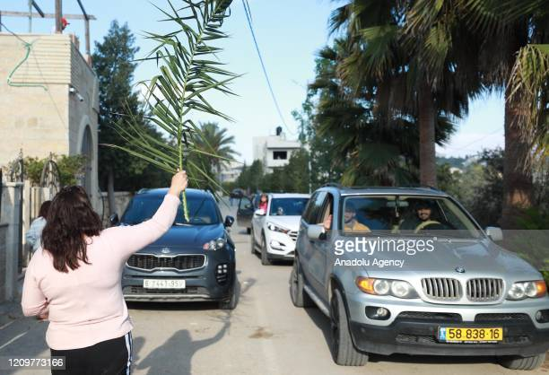 Members of the Eastern Orthodox Church attend the Palm Sunday procession amid coronavirus pandemic precautions in Ramallah West Bank on April 12 2020...